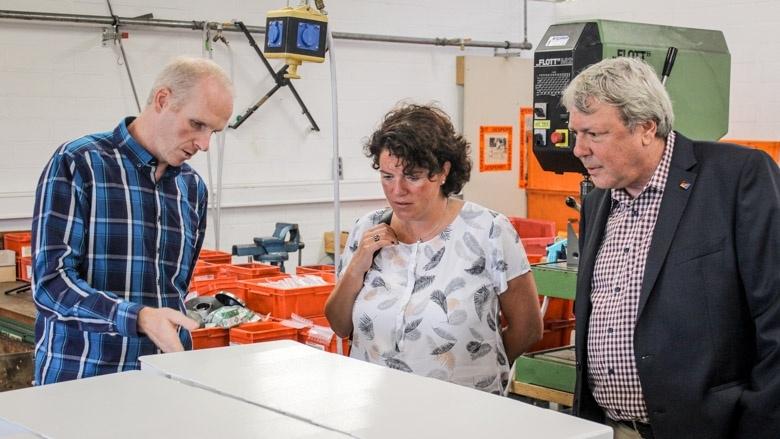 Werkstattleiter Thomas Plöger erläutert Kerstin Vieregge und Uwe Schummer die Abläufe